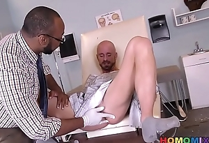 Black contaminate removing something from the arse of a white guy