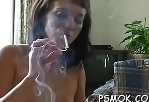 Hot babe bringing off in all directions a toy while having a smoke in couch